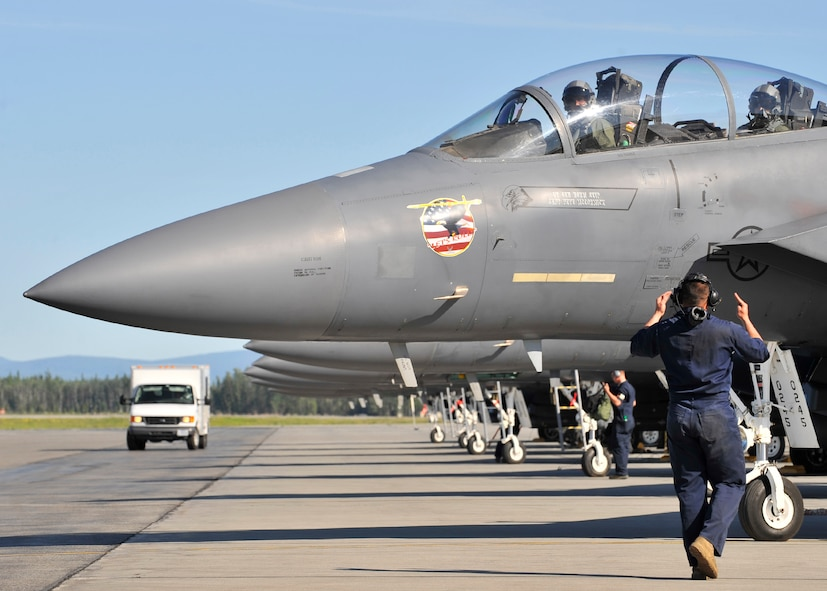 Senior Airman Cesar Zayas marshalls an F-15 Strike Eagle prior to take off during NORTHERN EDGE 2009 at Eielson Air Force Base, June 16. NE09 is an exercise designed to sharpen the U.S. Armed Forces' skills and develop interoperable plans and programs. Airman Zayas is a dedicated crew chief assigned to the 366th Aircraft Maintenance Squadron, Mountain Home AFB, Idaho. (U.S. Air Force photo/Staff Sgt. Christopher Boitz)