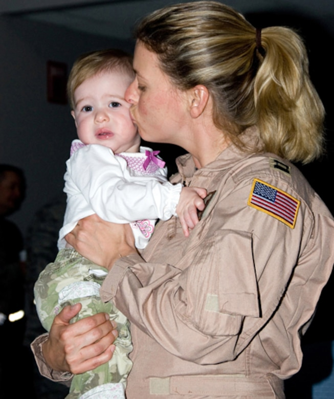 Capt. Becki Restrepo kisses her nine month old baby, Leona Grace, goodbye just before her departure. (U.S. Air Force photo by MSgt Shannon Bond) (RELEASED)