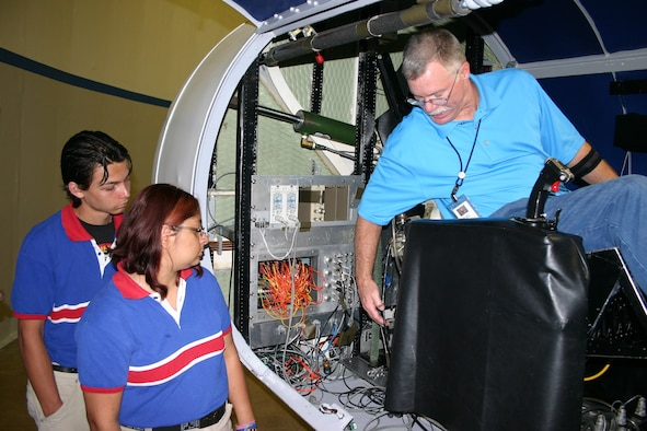 Mac Baker, a senior centrifuge technician at Brooks City-Base, Texas, demonstrates to Harmony Science Academy students the proper procedures for hooking test pilots up to a centrifuge canopy.  Centrifuge training runs test the ability of pilots to perform anti-G straining maneuvers while under extreme stress.  (U.S. Air Force photo/Richard Salomon)
