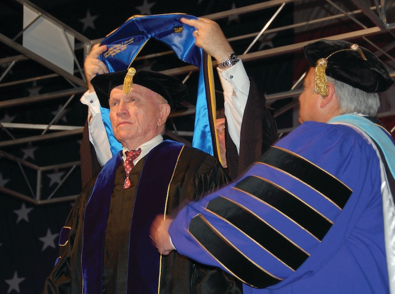 "Retired Col. Frank Borman receives his doctoral hood Saturday at the USAF Test Pilot School graduation ceremony as the second Air University honorary degree recipient presented by Lt. Gen. Allen G. Peck, the Air University commander. Colonel Borman, the ""dean of astronauts"" led the Apollo 8 mission as the first spacecraft to circle the moon. He was also a distinguished alumnus and former instructor at TPS. (U.S. Air Force photo/Senior Airman Melissa Copeland)"