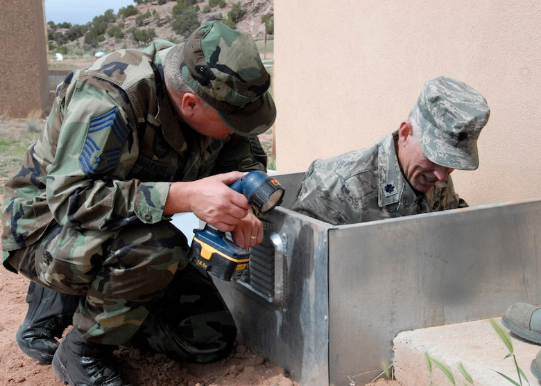 Chief Master Sgt. Leslie Watkins and Lt. Col. Thomas Niichel, 240th Civil Engineer Squadron, examine damage caused by the rain and mud on a newly-built dining hall at Saint Michael?s Association for Special Education June 8, 2009 near Window Rock, Az..