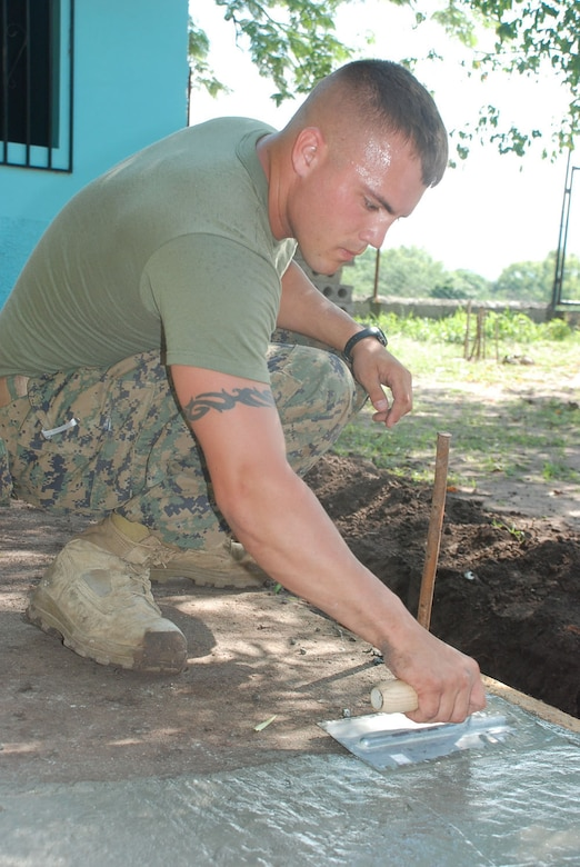 MIRA VALLE LA PAZ, Honduras - U.S. Marine Corps Lance Cpl. Casey Ruff puts the finishing touches on a sidewalk after running a water line to a school here from a water tower across the street.  The lance corporal is assigned to Alpha Company, 4th Combat Engineering Battalion in Crosslands, W.V.  He is here for three weeks with Beyond the Horizon, a large-scale exercise completing medical readiness missions and civil engineer projects throughout Central America.  (U.S. Air Force photo/ Tech. Sgt. Rebecca Danét)