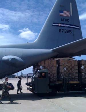Members of the 185th Air Mobility Wing begin loading four crates of children's wheelchairs onto a C-130 June 11, 2009, in Sioux City, Iowa. A C-130 aircrew from Air Force Reserve Command's 302nd Airlift Wing, Peterson Air Force Base, Colo., transported the wheelchairs to Andrews AFB, Md., where a larger cargo plane transported the wheelchairs to Baghdad, Iraq. (U.S. Air Force photo/Capt. Brian McReynolds)