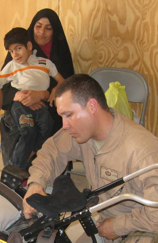 In this undated photo, an Airman helps custom fit a pediatric wheelchair for an Iraqi child. A C-130 aircrew from the Air Force Reserve's 302nd Airlift Wing, Peterson Air Force Base, Colo., flew wheelchairs like this one to Andrews AFB, Md., where another plane took the wheelchairs to Baghdad, Iraq. (Courtesy photo/Brad Blasuer)