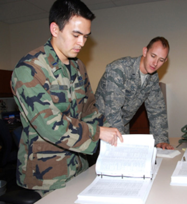 1st Lts. Sean Conley (left) and Charles Chapot, active duty airfield operation officer trainees, assigned to the 241st Air Traffic Control Squadron, look over air traffic controller manuals at the 241st ATCS. (U.S. Air Force photo by Staff Sgt. Michael Crane)
