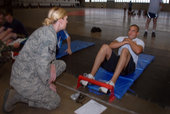 Senior Airman Hannah McGuire with the 28th Medical Group counts as Airman First Class Alex Carmona of the 137th Space Warning Squadron completes his sit-ups during his annual physical training (PT) June 10, 2009, Ellsworth Air Force Base, South Dakota.  Carmona along with other members of the 137th SWS located in Greeley Colorado, are participating in several training events to include there PT test while at Ellsworth AFB this week to further enhance their one of a kind worldwide capable mission as a missile warning , space launch and detection mobile unit. (U.S Air Force photo by: Tech. Sgt. Wolfram M. Stumpf)