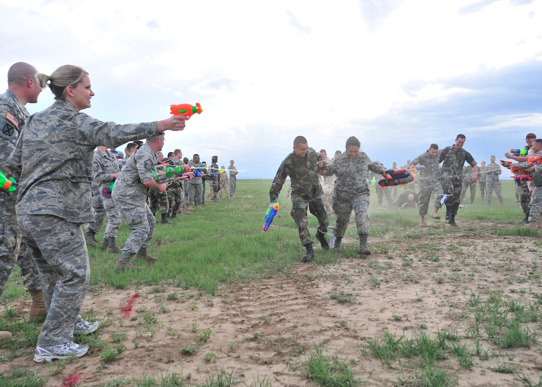 BUCKLEY AIR FORCE BASE, Colo. -- Two Airmen make their way through a line of water gun fire from other participants at the Combat Dining-in May 29 at Camp Rattlesnake here. More than 100 people showed up for the event. (U.S. Air Force photo by Senior Airman Alex Gochnour)