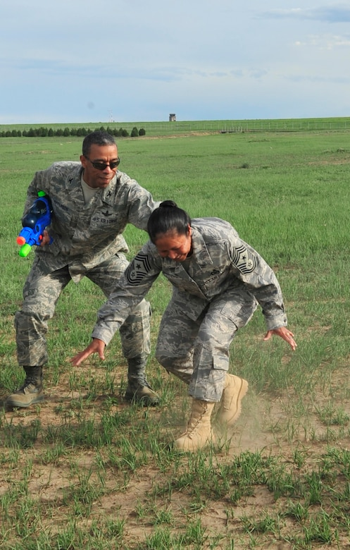 BUCKLEY AIR FORCE BASE, Colo. -- Col. Vincent Jefferson, 460th Mission Support Group commander, attempts to hold up Chief Master Sgt. Arleen Heath, 460th Space Wing Command Chief, after she spun around a bat as part of the obstacle course at the Combat Dining-in May 29 at Camp Rattlesnake here. More than 100 people showed up for the event. (U.S. Air Force photo by Senior Airman Alex Gochnour)