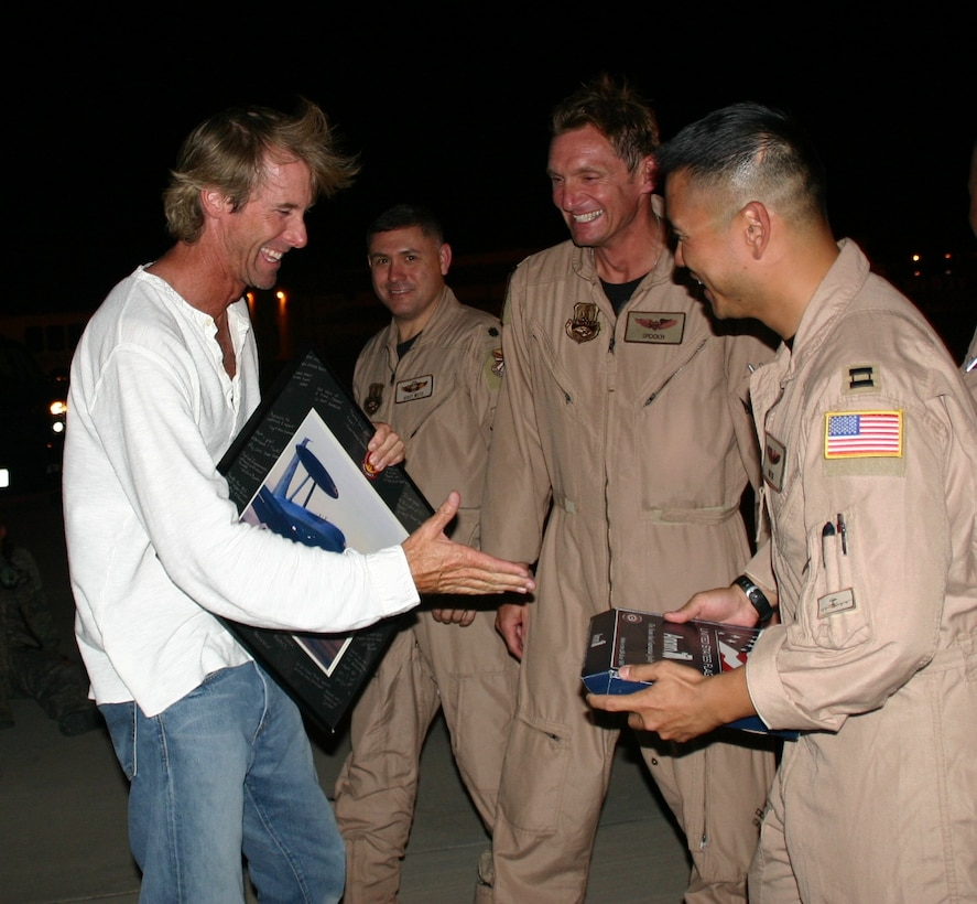 """As a token of appreciation, after filming on the E-3, Lt. Col. Jimmy Warren and Capt. Thomas Ikehara present Michael Bay, director of """"Transformers: Revenge of the Fallen,"""" with a framed picture of the E-3 and a flag flown on the jet during a combat sortie. Photo courtesy of 1st Lt. Kinder Blacke."""