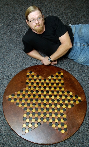 When not welding at Tinker, Mike Owen thinks chess. His idea that more than two could play the same chess game evolved and now waits for attorneys to patent his dream. His large, hand-made wooden gameboard accommodates six players. (Air Force photo by Margo Wright)