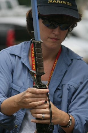 Lisa Dezzutti, president and chief executiive of Market Connections, holds an M16-A2 Service Rifle with a fixed bayonet June 19, during the Marine Corps Business Executive Forum. MCBEF is a strategic communication effort that exposes senior business representatives around the country to Marine Corps interests.