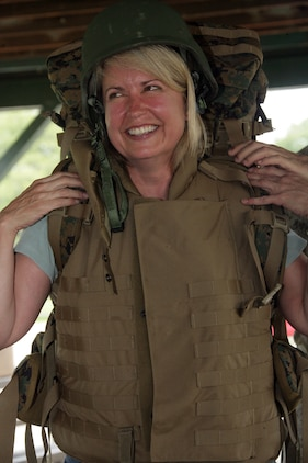 Gwyn Whittaker, president and chief executive of Mosiac Incorporated, tries on a full load of combat gear June 19, during the Marine Corps Business Executive Forum. MCBEF is a semi-annual strategic communication effort that exposes senior business representatives around the country to Marine Corps interests.