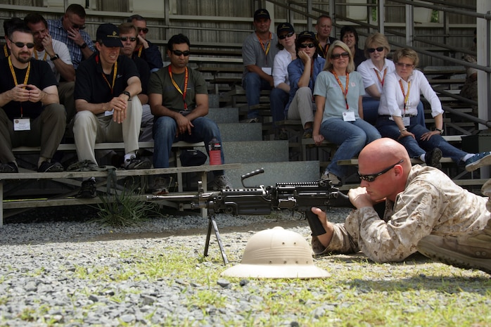 Members from the Maryland-based Vistage group listen and watch as a Marine marksmenship trainer show them the proper way to handle and fire the M249 Squad Automatic Weapon June 19. The Marine Corps Business Executive Forum provided the platform for senior business leaders to learn firsthand about the Marine Corps. MCBEF is a strategic communication effort that exposes senior business representatives around the country to Marine Corps interests.