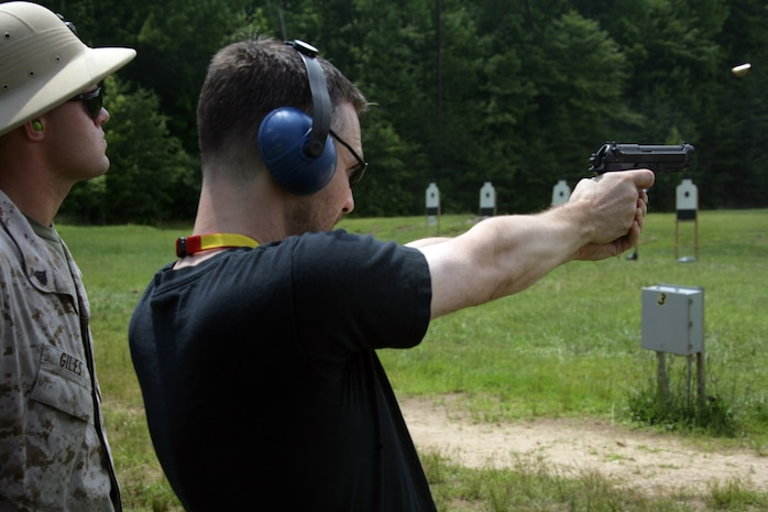 Michael D. Schader, chief executive of Yellow House Associates, fires the M9 pistol June 19, during the Marine Corps Business Executive Forum. The executives fired several weapons from the Marine Corps aresenal. Their day spent with Marines also included a tour of the Pentagon and the National Museum of the Marine Corps.