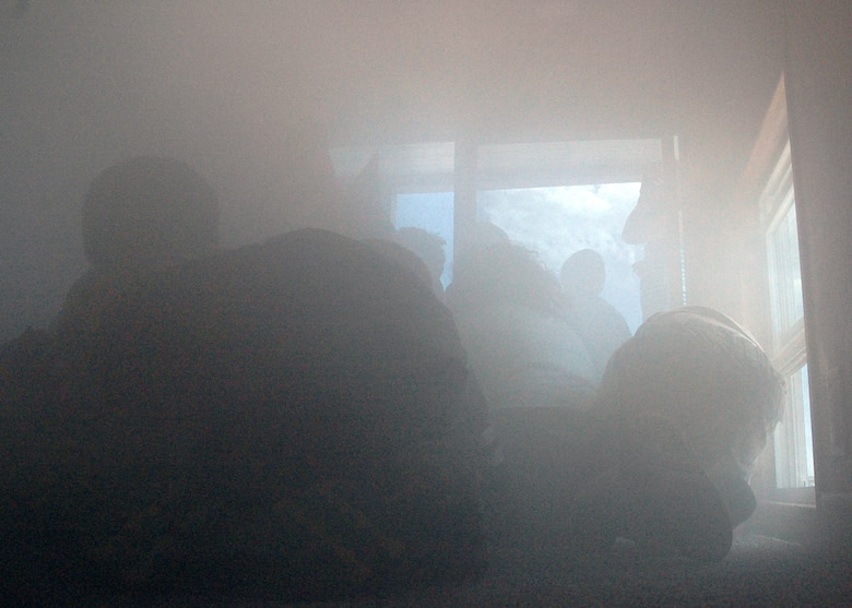 BUCKLEY AIR FORCE BASE, Colo. -- Children of Team Buckley employees evacuate the Buckley Fire Department's Training Smokehouse at the Military Family Appreciation Day at the base softball fields, June 6. The smokehouse teaches children what to do in case of a fire. An estimated 2,000 people enjoyed the festivities sponsored by Buckley's Integrated Delivery Services and the 460th Space Communications Squadron partnered with the United Service Organizations, United States Automobile Association and Operation Kids. (U.S. Air Force photo by Staff Sgt. Sanjay Allen)