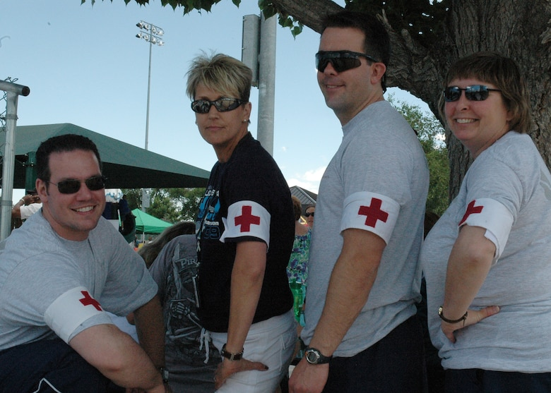BUCKLEY AIR FORCE BASE, Colo. -- Capt. James Moses, Sara Wineland, Tech. Sgt. Ryan Harding and Maj. Vicki Fair, all from the 460th Medical Group, were on hand as part of a first-response team at the Military Family Appreciation Day at the base softball fields, June 6. An estimated 2,000 people enjoyed the festivities sponsored by Buckley's Integrated Delivery Services and the 460th Space Communications Squadron partnered with the United Service Organizations, United States Automobile Association and Operation Kids. (U.S. Air Force photo by Staff Sgt. Sanjay Allen)