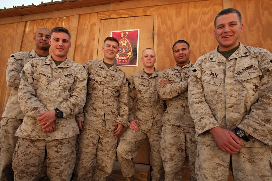 Marines with Intelligence section, Headquarters Company, Regimental Combat Team 8, stand proudly outside of their workspace during the early morning hours of shift changeover.  These Marines continuously collect and analyze information to make sure that RCT-8 Marines and attachments are well prepared for weather problems, any unsafe routes due to improvised explosive device activity and also provide data based information on the regiment's area of operations.