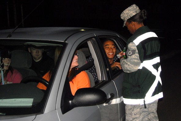 Staff Sgt. Corina Gross from the Tier Two hands out Ride for Life cards to 52nd Fighter Wing members June 19, 2009, as they exit Bitburg Air Base. Chief's Group, First Sgts.,Top III and First Four members were also on hand from 9 p.m. until 3 a.m. to remind Sabers to be safe and make responsible choices during the weekend.   (U.S. Air Force photo by Senior Master Sgt. Valerie J. Weaver)