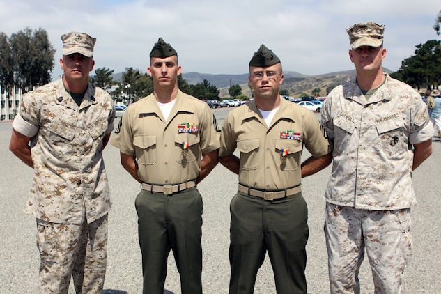 (From left to right) Sgt. Maj. Anthony Cruz Jr., sergeant major, Marine Combat Training Battalion, Staff Sgts. Shawn M. Martin and Jason M. Kuehnl, and Lt. Col.  John J. Carroll, commanding officer, MCT Bn. pose for a photo. The two staff sergeants were awarded the Navy and Marine Corps Medals during a graduation ceremony at the School of Infantry West, June 23. On two separate occasions, the Marines immediately responded to improper M67 fragmentation grenade throwing techniques and saved the lives of their students with no regard to their own lives.