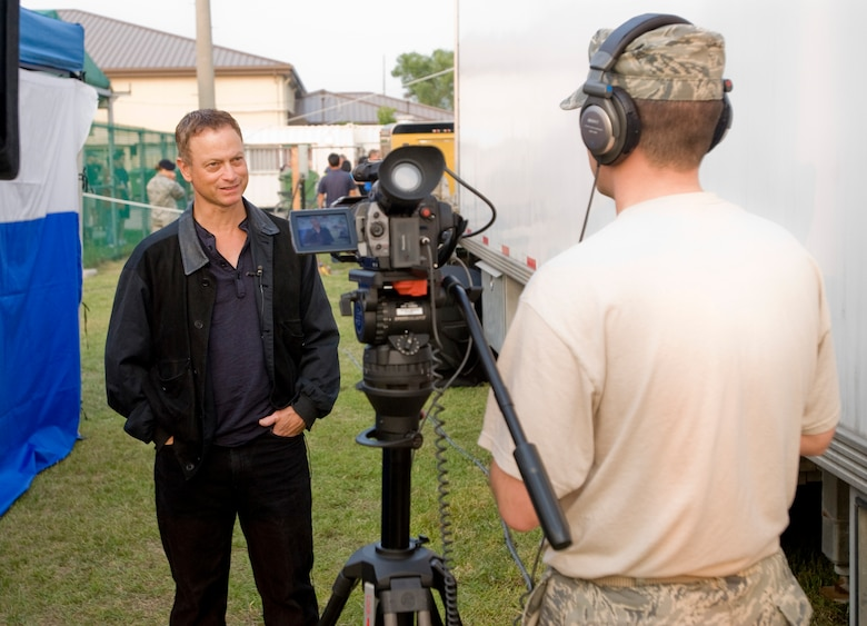 KUNSAN AIR BASE, Republic of Korea -- Gary Sinise, the bassist for Lt. Dan Band, gives an interview to Staff Sgt. Michael Schocker, Armed Forces Network Korea, about why he and his band do shows for the troops June 24. The Lt. Dan Band stopped at the Wolf Pack as part of their Asia USO tour. (U.S. Air Force photo by Senior Airman Jonathan Steffen)