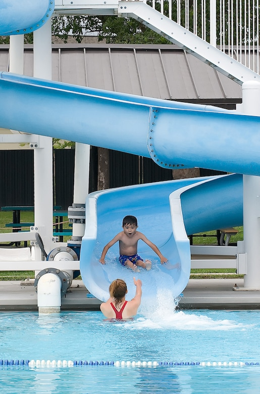 Emily Kolakowski, an Oasis Pool swimming instructor, prepares to catch Liam Wallace, one of her students, as he glides down their water slide at Dover Air Force Base June 23. The children get to finish their daily half hour swimming lesson with a fun-filled splash on the slide. (U.S. Air Force photo/Tom Randle)
