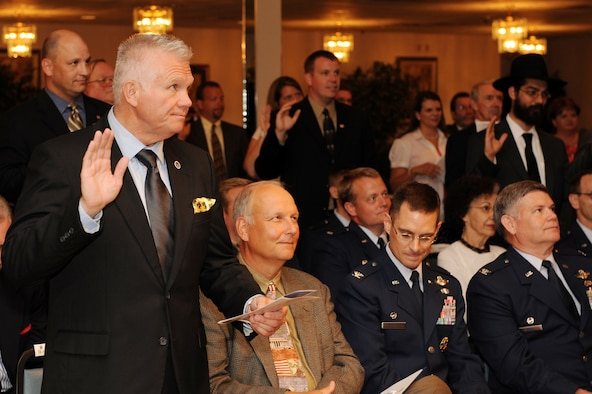 Mr. Phil Davis, 19th Airlift Wing honorary commander, and other honorary commanders, swear in during an honorary commander's induction ceremony at Hangar 1080 Monday. The Honorary Commanders' Program is a community outreach effort to continue building relationships between local civic leaders and Little Rock Air Force Base. The program allows community representatives to become more aware of the base's mission while offering military commanders and their unit members more insight into the communities in which they live. (U. S. Air Force photo by Senior Airman Jim Araos)