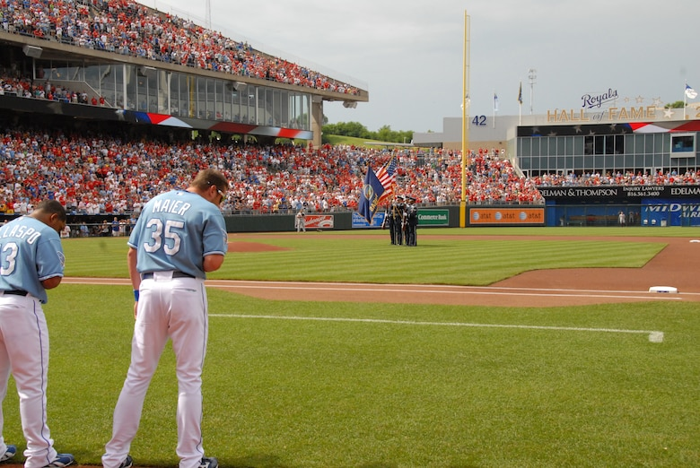 062009-F-6174J-016- Kansas City Royals Players Alberto Callaspo and Mitch Maier along with fans remove their caps for the national anthem at Kaufman Stadium while the 184th Intelligence Wing Honor Guard present the colors before their game against the St Louis Cardinals on June 20, 2009.                     (Photo By: SSgt Justin Jacobs)