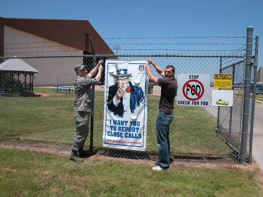 """Senior Master Sgt. Gary Bristol and James Templeman from the 507 Air Refueling Wing Safety Office post a new safety poster next to the flightline entry control point.  The poster is part of a new Air Force Safety Campaign to report potential accident """"Close Calls."""""""