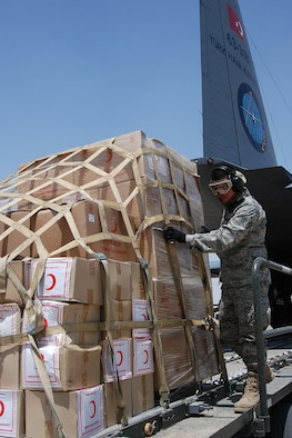 KIRKUK REGIONAL AIR BASE, Iraq – Staff Sgt. Jesus Aguilar, 506th Expeditionary Logistics Squadron Aerial Port Squadron ramp commander, pushes one of five cargo pallets loaded with relief supplies on to a 60K loader from a Turkish C-130 here June 22. Sergeant Aguilar was one of almost 20 ELRS Airmen involved in the download of 12 tons of supplies including 90 blankets, 400 tents, kitchen equipment, food and more. ELRS aerial porters also helped reconfigure the airplane to carry the 11 patients, who were victims of a June 20 suicide truck bombing in Taza District south of Kirkuk city. More than 80 people were killed and 250 injured in the blast. Sergeant Aguilar is a native of Riverside, Calif., and is deployed here from the 50th Aerial Port Squadron, March Air Reserve Base, Calif. (U.S. Air Force photo / Senior Master Sgt. Michael Land)