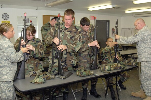 Master Sgt. Larry Shenold, Combat Readiness School, far right and 2nd Lt. Ashley Hardwick, 31st Combat Communications Squadron, introduce Air Force Academy cadets to the M-16 rifle during an Operation Air Force visit to Tinker. The program is meant to expose cadets to different facets of the service before they graduate.  (Air Force photo by Margo Wright)