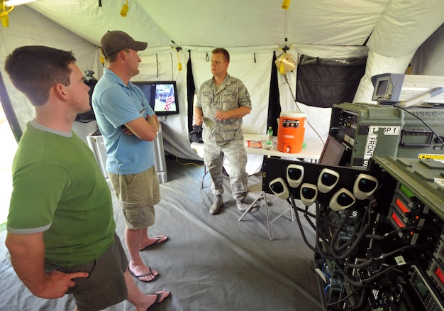 Chief Master Sgt.  Don Johnson of the 151st Communication Squadron, Utah Air National Guard, talks with Scott Stein of Murray (left) and Kelly Dansie of Salt Lake City, Utah about the Joint Incident Site Communication Center (JISCC) at Pioneer Park during Air Force Week June 1.  The JISCC allows the UTANG and Utah Army NG to provide communications with multiple government and civilian agencies during times of disasters by linking multiple radio frequencies and phone lines at the same time.   Pioneer Park in Salt Lake City was one of the locations for the public to meet and learn about the Air Force capabilities during AF Week June 1 ? 7, 2009.  U.S. Air Force photo by Tech. Sgt. Michael D Evans.