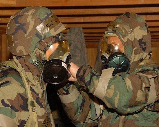 The 130th Engineering Installation Squadron held a super drill at Wendover Air Field, Wendover, Utah June 4-7 in preparation for their upcoming Operational Readiness Inspection. Tech. Sgt. Gregory Taylor assists Tech. Sgt. Jason Wolf with his chemical mask during a MOPP 4 drill. For four days the 130th EIS reenacted several mock chemical attacks where they practiced donning chemical gear, searching for unexploded ordinances and patrolling the area for toxic levels of chemical agents.  U.S. Air Force photo by Staff Sgt. Emily Monson.