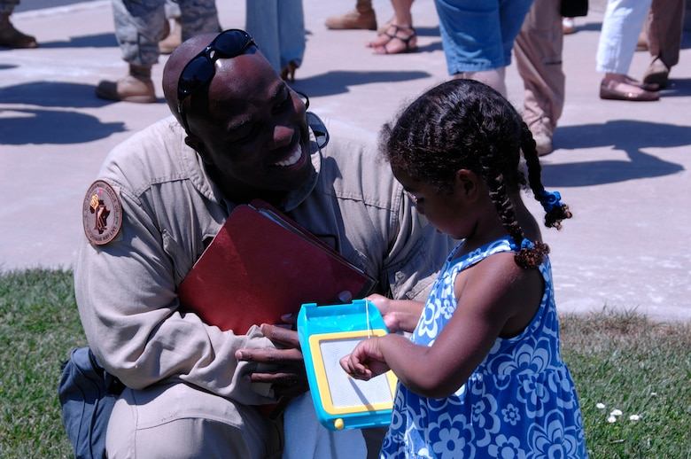 Tech. Sgt. Elliot Paige, an MC-130P Combat Shadow radio operator from the 130th Rescue Squadron, is welcomed home at Moffett Federal Airfield, Calif., by his daughter after a 40 day deployment to Djibouti June 18. (Air National Guard photy by Chief Master Sgt. Chris Hartman)(RELEASED)