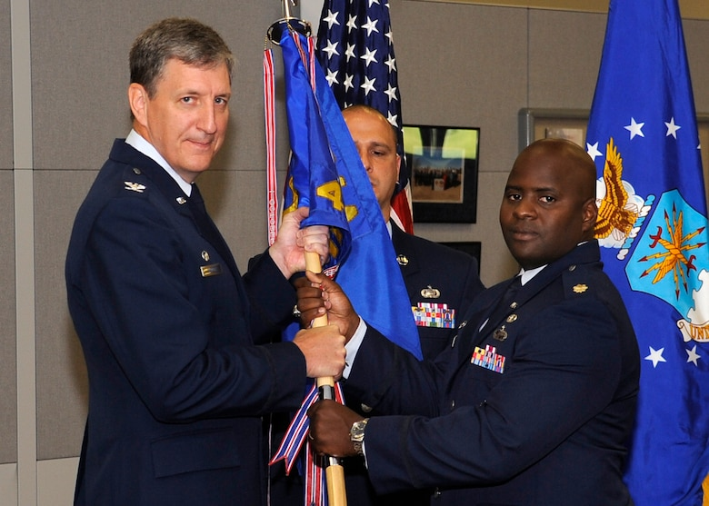 BUCKLEY AIR FORCE BASE, Colo. – Col. Daniel Badger Jr., Air Force Manpower Agency commander, passes command of the 4th Manpower Requirements Squadron over to Maj. Ernest Wearren Jr. in a change of command ceremony at the Air Reserve Personnel Center, June 22. (U.S. Air Force photo by: Senior Airman Steven Czyz)