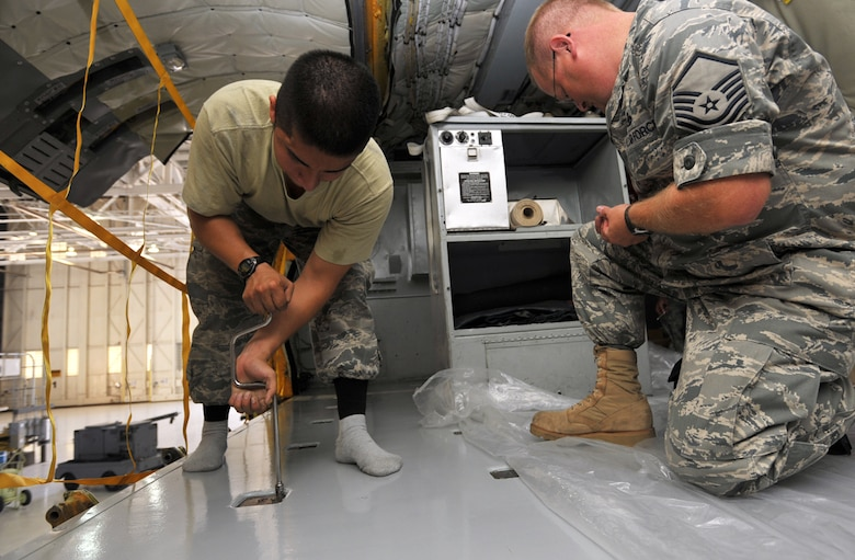 "Senior Airman Gilberto Rodriguez-Martinez (on left) works in his socks and Master Sgt. Al Ryder steps on plastic to protect a new coat of paint to the floor of a KC-135 Stratotanker scheduled for competitions at Air Mobility Rodeo 2009. Both maintainers are assigned to a ""blended"" team of Reserve and Regular (active-duty) Airmen preparing to represent McConnell Air Force Base, Kan., as a total force at the biennial readiness competition. Sergeant Ryder is a Reservist assigned to the 931st Aircraft Maintenance Squadron. Airman Rodriguez-Martinez is an active-duty Airman assigned to the 22nd Aircraft Maintenance Squadron. (U.S. Air Force photo/Tech. Sgt. Jason Schaap)"