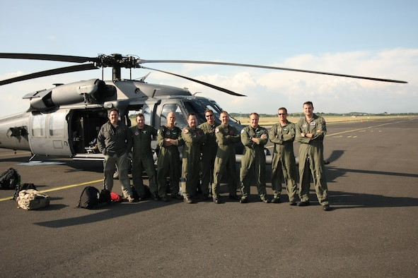 Airmen of the 56th Rescue Squadron at RAF Lakenheath, England, pose in front of one of the two HH-60G Pave Hawks used in a rescue mission off the West coast of Ireland, June 26. The pararescue specialists and crew hoisted a sailor in need of emergent medical care onto their helicopter from the cargo ship, Pascha. The man was experiencing severe abdominal pain, requiring immediate medical evacuation. Two additional U.S. Air Force aircraft, a KC-135R Stratotanker from the 100th Air Refueling Wing and a MC-130P Combat Shadow from the 352nd Special Operations Group -- both from nearby RAF Mildenhall -- supported the operation for refueling and communication purposes. A Nimrod, search and rescue aircraft, from the United Kingdom also played a critical role in the operation, providing real time communication and coordination between the ship and USAF aircraft. The patient was delivered to an awaiting ambulance in Shannon, Ireland, and is in stable condition. (U.S. Air Force photo / Senior Airmen Michael Barber)