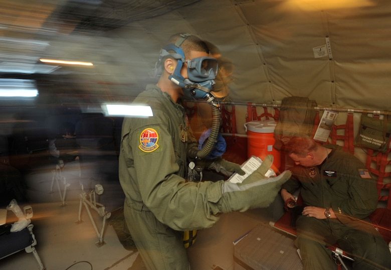 Senior Airman Elvin Paulino rushes to fight a simulated in-flight fire in the rear of a KC-135 Stratotanker Sunday. The simulation was part of a three-day aeromedical evacuation training mission using a KC-135 flown by Airmen from the 931st Air Refueling Group. Airman Paulino is assigned to the 514th Aeromedical Evacuation Squadron at McGuire Air Force Base, N.J. (U.S. Air Force photo/Tech Sgt. Jason Schaap)