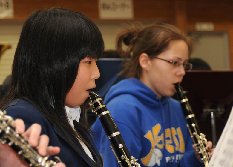 """FUSSA CITY, Japan- Iwama Yukina, a student at Fussa Daiichi Junior High School, and Brianna Briggs, a student at Yokota High School, practice a piece of music together March 2 at the junior high school. The junior high and high school bands will combine to perform three pieces of music at a Japan-U.S. Joint Concert """"Music Across the Border"""" at 3 p.m. March 15 at the Fussa Citizens' Hall. (U.S. Air Force photo/Airman Sean Martin)"""