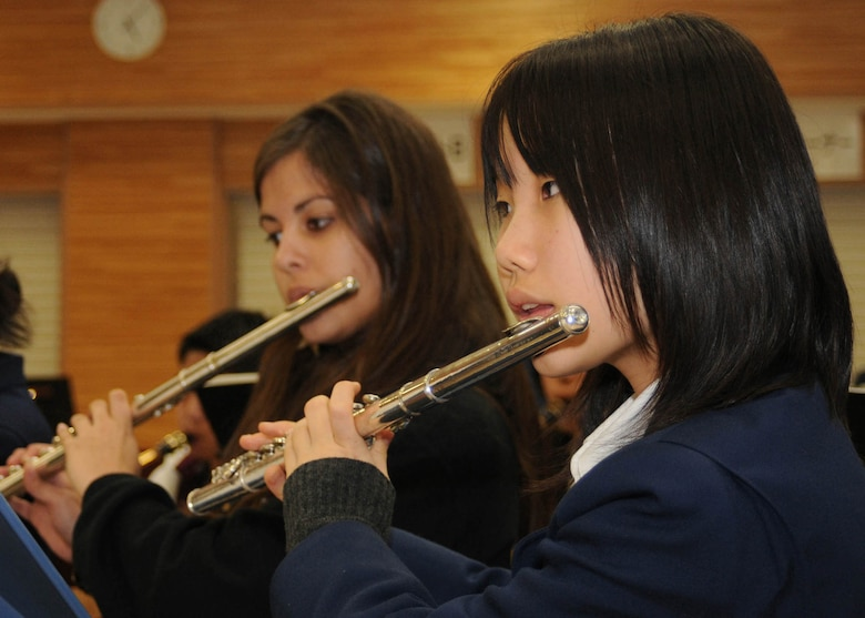 """FUSSA CITY, Japan- Haruka Ishikawa, a student at Fussa Daiichi Junior High School, and Rachell Sanchez-Aizpru'a, a student at Yokota High School, practice a piece of music together March 2 at the junior high school. The junior high and high school bands will combine to perform three pieces of music at a Japan-U.S. Joint Concert """"Music Across the Border"""" at 3 p.m. March 15 at the Fussa Citizens' Hall. (U.S. Air Force photo/Airman Sean Martin)"""