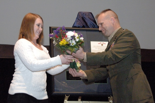 Army Lt. Col. Eric Garretty, the Montgomery Military Entrance Processing Station commander, presents flowers to Miranda Bicknell, widow of Pfc. Stephen Bicknell, during a ceremony at the Senior Non-Commissioned Officer Academy here Feb. 20. A native of Prattville, Ala., Private Bicknell died while serving in Iraq in October 2006. (Air Force photo by Donna Burnett)