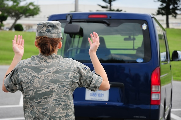 Airman 1st Class Amanda Grabiec, 18th Wing Public Affairs, demonstrates the proper technique to spot a vehicle while reversing at Kadena Air Base, Japan, March 4, 2009. Simple safety precautions such as this can reduce the number of preventable traffic accidents involving government vehicles. (U.S. Air Force photo/Airman 1st Class Chad Warren)