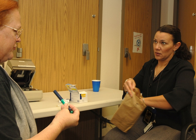 Mrs. Ellen Kilpatrick, diabetes educator and registered nurse (right), explains the proper use of an Insulin pen while distributing medicines and counseling a patient in the Diabetes Education Class at Wilford Hall Medical Center March 2. (U.S. Air Force Photo By Senior Airman Josie Kemp)