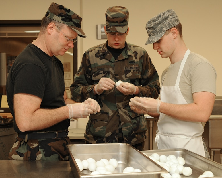 (Left to right) Master Sgt. John Gobler, Airman 1st Class Andrew Combs and Staff Sgt. Jamey Kuske  peel more than four dozen hard boiled eggs for the salad bar. (U.S. Air Force photos by Master Sgt. Paul Gorman)