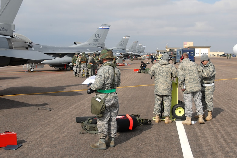 Members of the 140th Wing, Colorado Air National Guard, undergo maintenance procedures to ensure that the F-16C aircraft are ready for war during a Phase 1 Operational Readiness Inspection at Buckley Air Force Base.  Inspectors are everpresent and study notes at the fire supression bottle (right).  (Photo by SMSgt John Rohrer, 140th Wing Public Affairs)