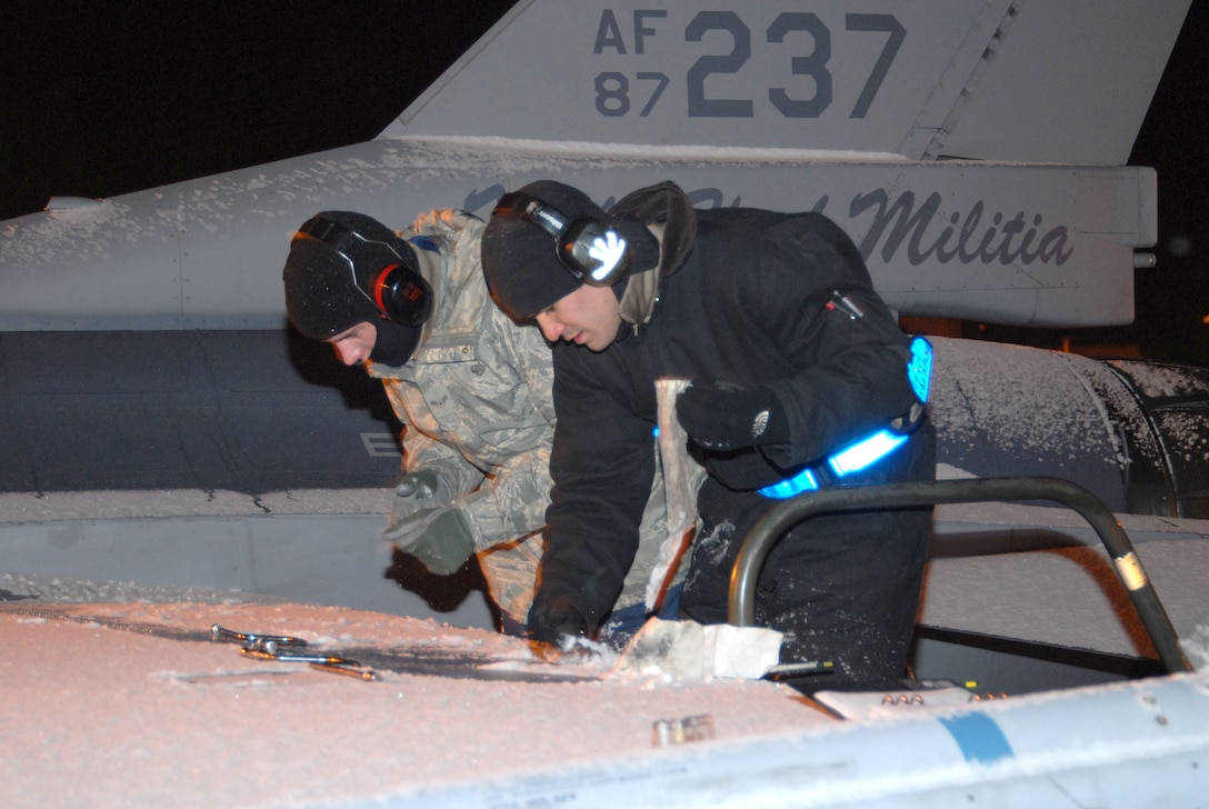 A1C Austin Smith and SSgt Brandon Ginn of the 140th Wing Maintenance section fasten down a panel on an F-16C aircraft as part of the Generation phase of the Operational Readiness Inspection.  (Photo by SMSgt John Rohrer, 140th Wing Public Affairs)