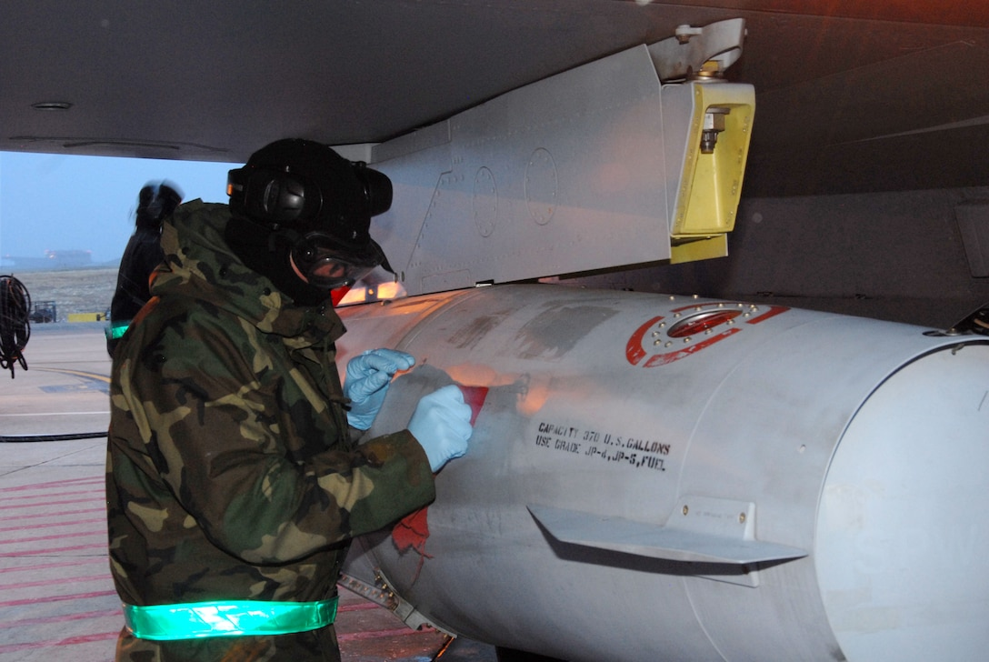 Phase Dock personnel wipe down a fuel tank on an F-16C model aircraft during an Operational Readiness Inspection at the 140th Wing, Colorado Air National Guard.  As part of the generation phase of the inspection, members braved the cold and snow as they ensure that all required aircraft are ready to deploy to a mock forward operation base.  (Photo by SMSgt John Rohrer, 140th Wing Public Affairs)
