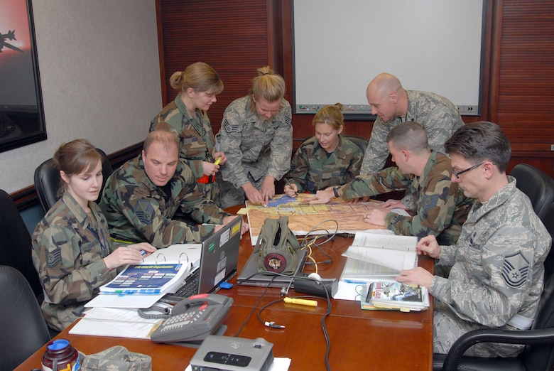140th Wing Operation Support Squadron Intel Personnel Prepare for Briefs During an Operational Readiness Inspection.  They will be briefing the Commanders on the deployment orders as well as the pilots on the preferred routes for flight to their destination.  (Photo by SMSgt John Rohrer, 140th Wing Public Affairs)