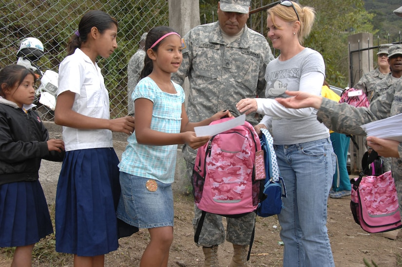 Give a Kid a Backpack Foundation volunteer Amy Vazquez and Army Sgt. Wirient Cuevas-Salas, Joint Task Force-Bravo Civil Affairs, pass out backpacks Feb. 24 at Escula Nuevo Mundo in El Encinal, Honduras.  (U.S. Army photo/Specialist Christopher Wellner)
