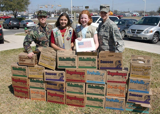 Tech. Sgt. Shauna Walker and Staff Sgt. Sunshine Scarbrough (far right), Air Force Personnel Center community outreach coordinators, receive 515 boxes of Girl Scout cookies from Samantha Frank and Madison Albrecht, Girl Scout Troop 2642 members, March 4 at Randolph Air Force Base, Texas. The 12-year-old girls raised the money to purchase the cookies from local businesses and community members. Each box has an original poem written by Albrecht thanking the servicemembers for their sacrifice and service to the nation. These cookies will be shipped to deployed servicemembers in Iraq, Afghanistan, and other countries in the Middle East. This is the second year Albrecht has raised money to purchase Girl Scout cookies for deployed servicemembers.