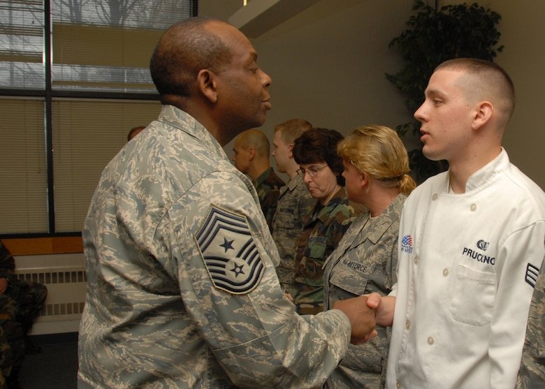 New York State Command Chief Master Sergeant Hardy Pierce Jr. presents U. S. Air Force Senior Airman James Pruckno a coin at the 174th Fighter Wing Syracuse New York. The coin was for his hard work and dedication throughout the year in ensuring mission successfulness. US Air Force Photo SSgt Ricky Best